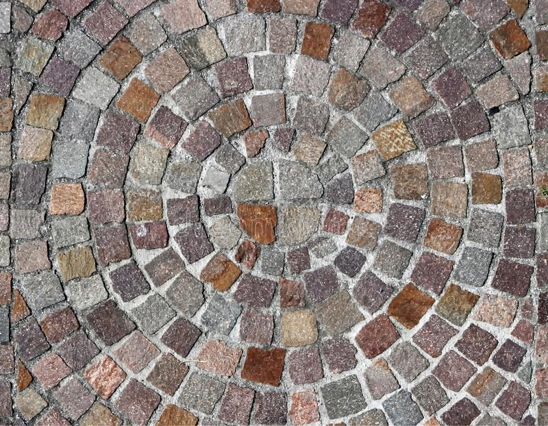 Outdoor stone flooring of porphyry cubes made with a round design, with circles that becomes larger starting from the center stock image