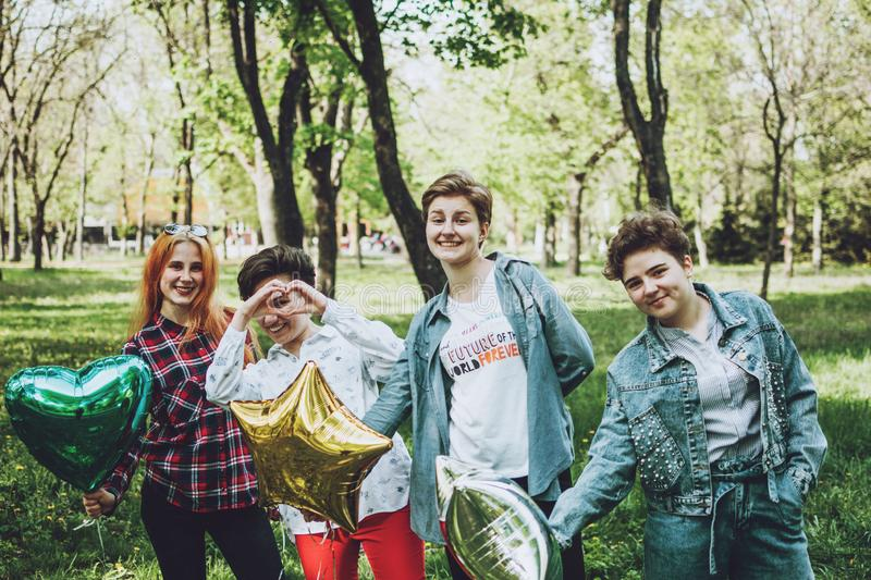 Outdoor student party. Group of smiling cheerful girl friends celebrating a party with balloons in park stock photography
