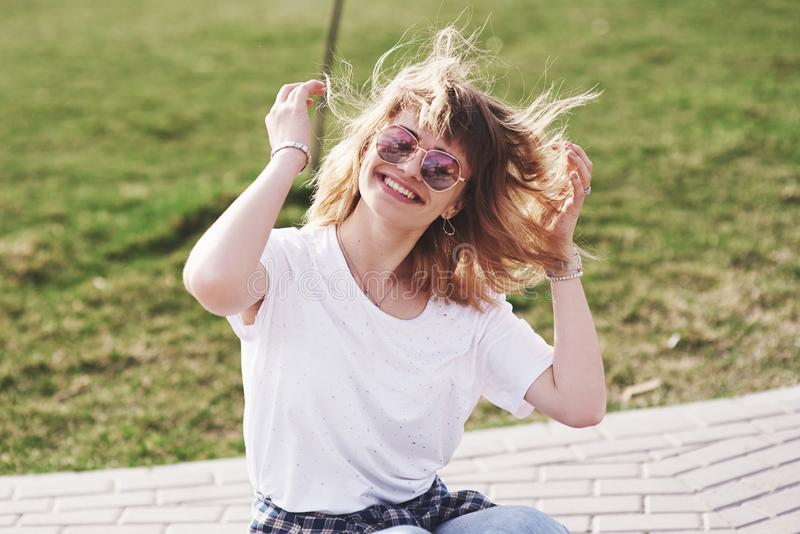 Outdoor summer lifestyle image of young pretty hipster woman having fun. Soft sunny colors royalty free stock images