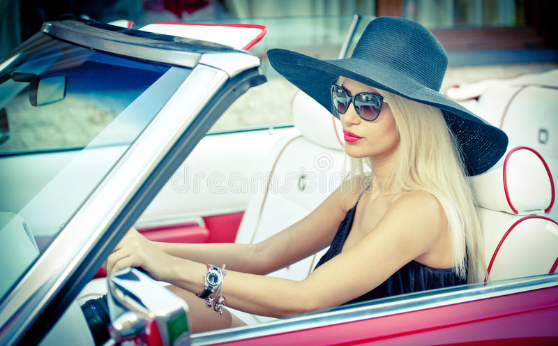 Outdoor summer portrait of stylish blonde vintage woman driving a convertible red retro car. Fashionable attractive fair hair girl royalty free stock photos