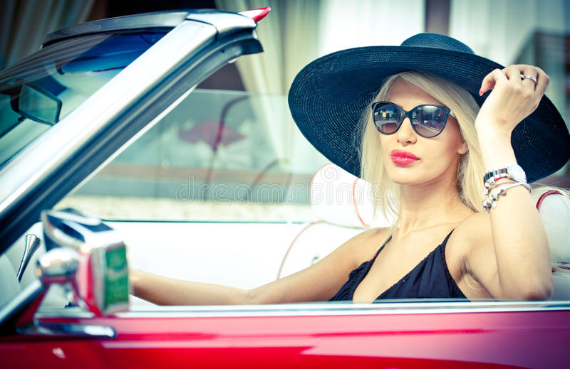 Outdoor summer portrait of stylish blonde vintage woman driving a convertible red retro car. Fashionable attractive fair hair girl royalty free stock image
