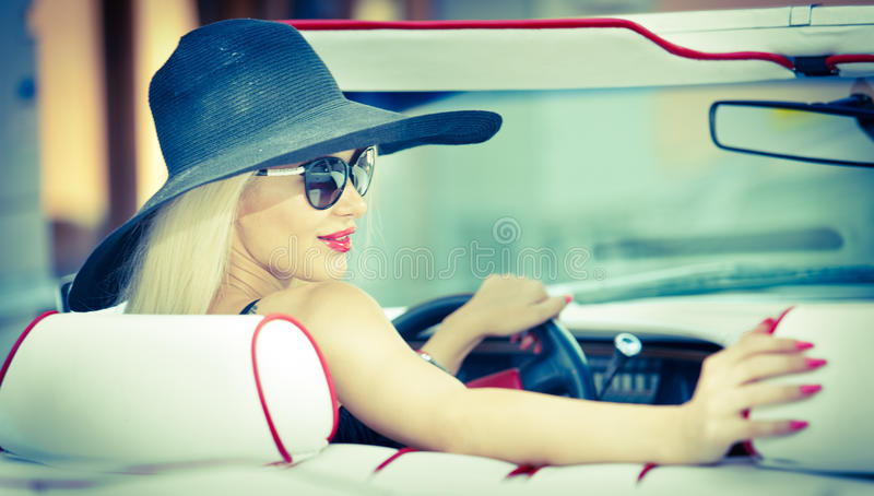 Outdoor summer portrait of stylish blonde vintage woman driving a convertible red retro car. Fashionable attractive fair hair girl. Outdoor summer portrait of royalty free stock images
