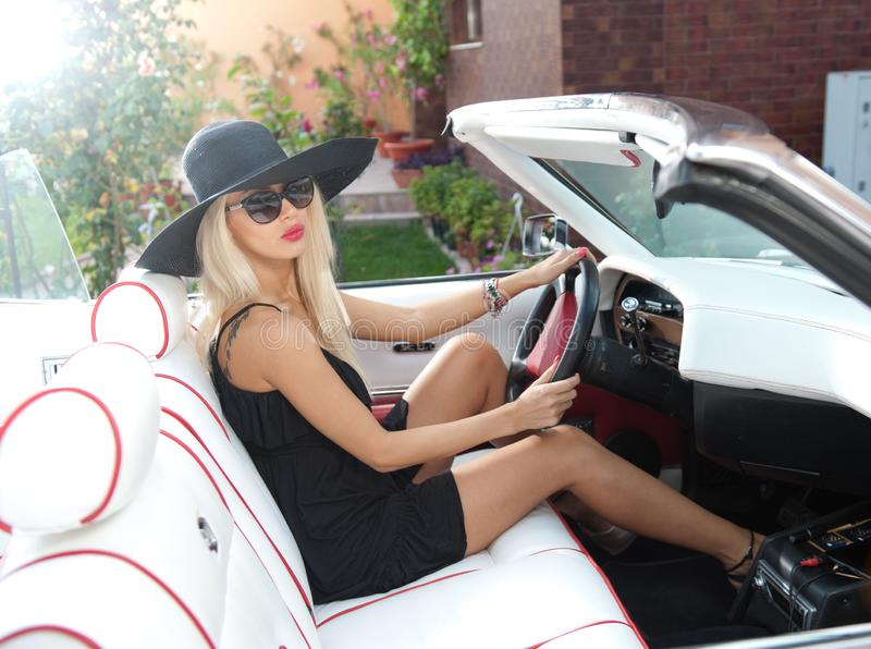 Outdoor summer portrait of stylish blonde vintage woman driving a convertible retro car. Fashionable attractive fair hair female royalty free stock photography