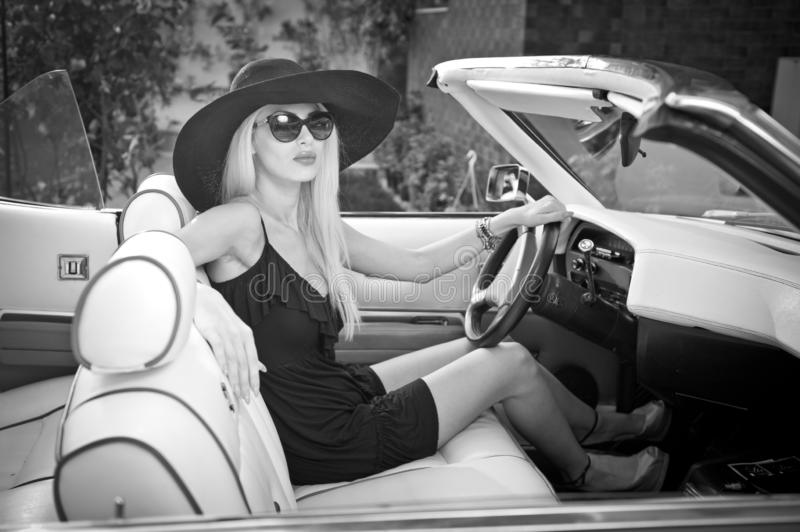 Outdoor summer portrait of stylish blonde vintage woman driving a convertible retro car. Fashionable attractive fair hair female stock photos