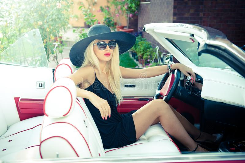 Outdoor summer portrait of stylish blonde vintage woman driving a convertible retro car. Fashionable attractive fair hair female stock photography