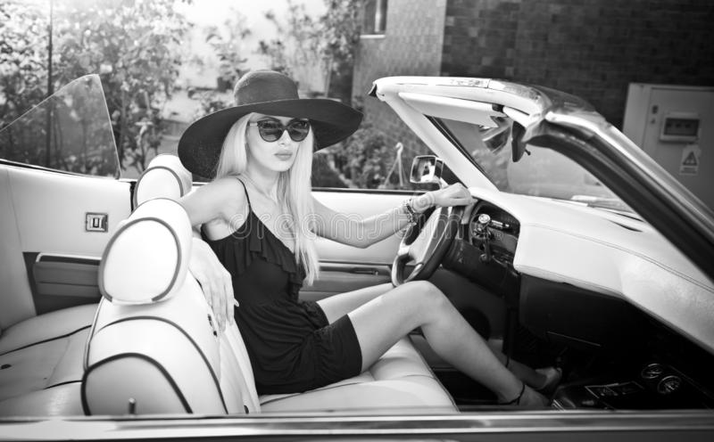 Outdoor summer portrait of stylish blonde vintage woman driving a convertible retro car. Fashionable attractive fair hair female stock image