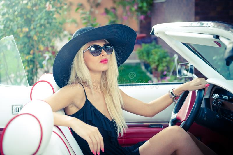 Outdoor summer portrait of stylish blonde vintage woman driving a convertible retro car. Fashionable attractive fair hair female stock images