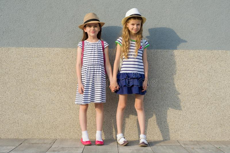 Outdoor summer portrait of two happy girl friends 7, 8 years holding hands. Girls in striped dresses, hats with backpack, royalty free stock images
