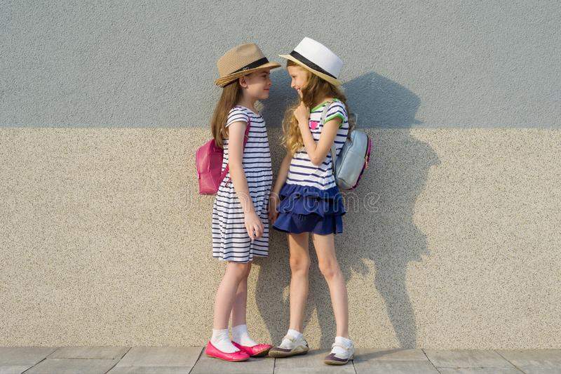 Outdoor summer portrait of two happy girl friends 7,8 years in profile talking and laughing. Girls in striped dresses, hats with royalty free stock images