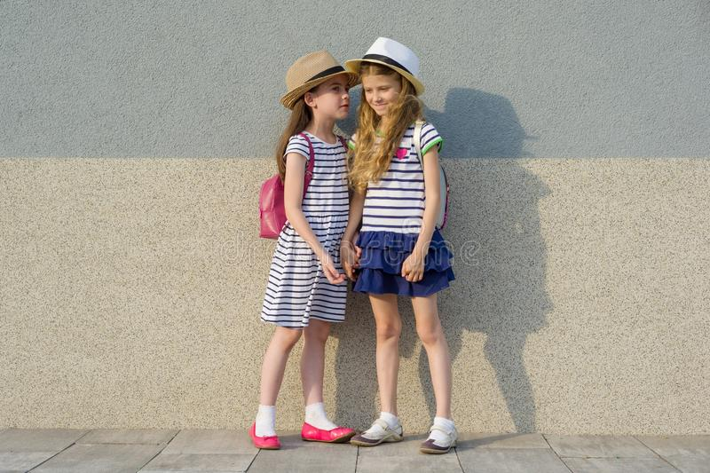 Outdoor summer portrait of two happy girl friends 7,8 years in profile talking and laughing. Girls in striped dresses, hats with. Backpack, background gray wall royalty free stock photography
