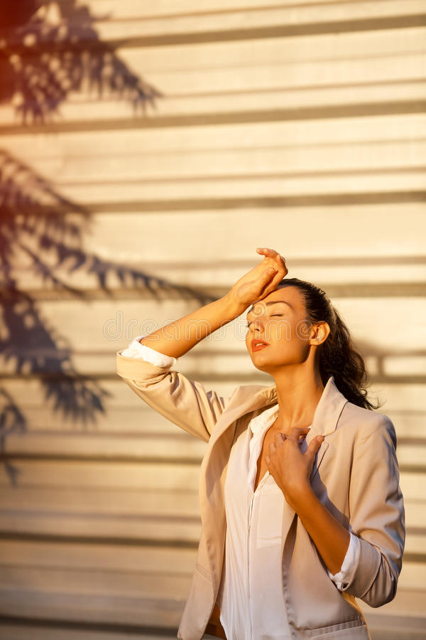 Outdoor summer portrait of young girl in suit suffering sun heat. Beautiful business woman at street in hot day. Time to travel concept. Outdoor summer portrait stock image