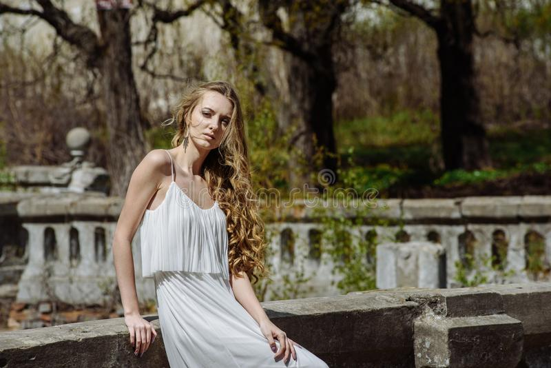 Outdoor summer portrait of young pretty cute girl. Beautiful woman posing at old bridge. in white dess standing near stone railin stock photography