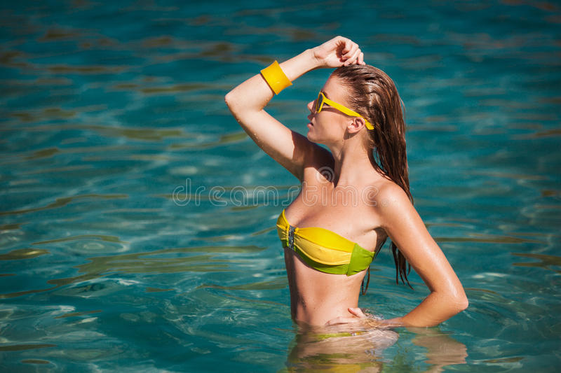 Outdoor summer portrait of young pretty woman in bikini near the sea at tropical beach. Outdoor summer portrait of young pretty woman in bikini near the sea at stock photo