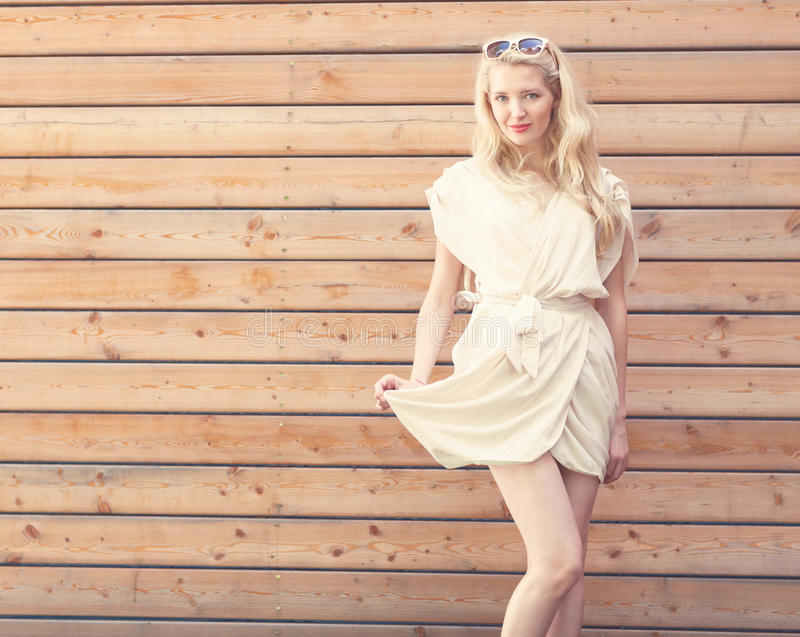 Outdoor summer sensual fashion portrait beautiful young blond woman lifts the edge of a white dress standing on the background of royalty free stock photography