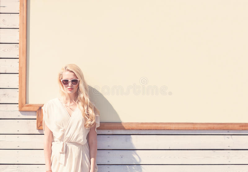 Outdoor summer sensual fashion portrait beautiful young blond woman of a white dress in sunglasses on the street on the background stock photography