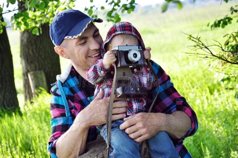 Outdoor summer smiling lifestyle portrait of happy father and little baby girl having fun with retro camera travel photo royalty free stock image