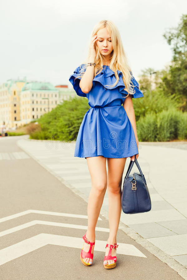 Outdoor summer smiling lifestyle portrait of pretty young woman with big blue handbag. Long blond hairs, blue outfit in royalty free stock images