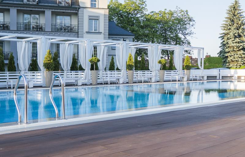 Outdoor sunny swimming pool of luxury hotel and resort with a beautifull clean blue water with a stairs. Outdoor sunny swimming pool of luxury hotel and resort stock photo
