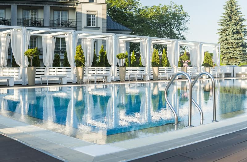 Outdoor sunny swimming pool of luxury hotel and resort with a beautifull clean blue water with a stairs. Outdoor sunny swimming pool of luxury hotel and resort stock image