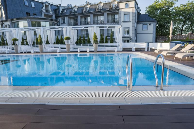 Outdoor sunny swimming pool of luxury hotel and resort with a beautifull clean blue water with a stairs. Outdoor sunny swimming pool of luxury hotel and resort royalty free stock images