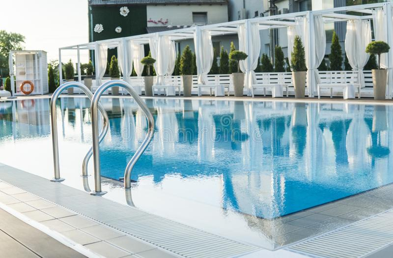 Outdoor sunny swimming pool of luxury hotel and resort with a beautifull clean blue water with a stairs. Outdoor sunny swimming pool of luxury hotel and resort royalty free stock photography