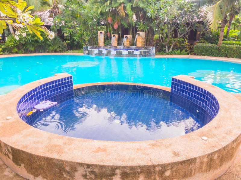 Outdoor swimmimg pool. Outdoor swimming pool with waterfall royalty free stock photo