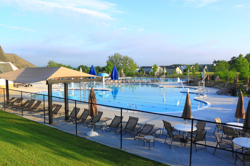 Outdoor Swimming Pool. Large community outdoor swimming pool with furniture on blue sky background stock photography