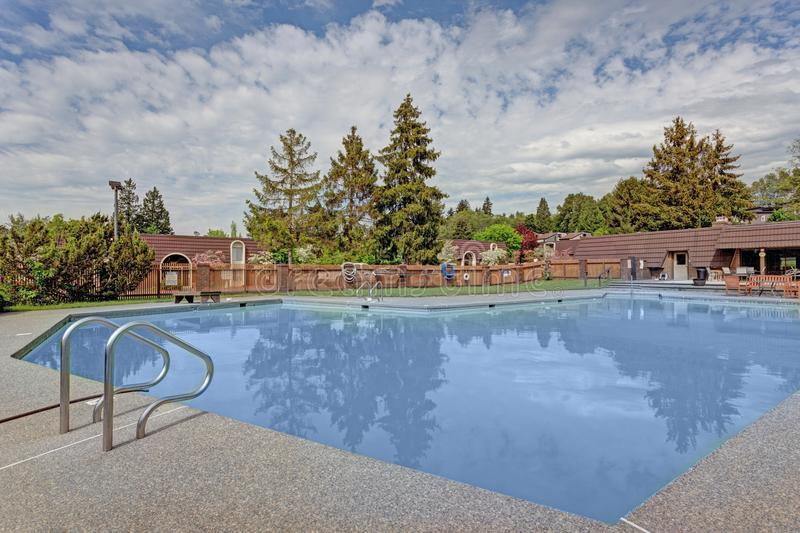 Outdoor swimming pool at apartment complex. Outdoor swimming pool at condominium building during summer day royalty free stock photography