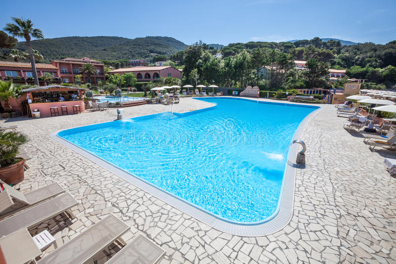Outdoor Swimming Pool. A swimming pool and outdoor spa with poolside. Hills and green trees in the distance. Location: Procchio, Elba Island. Italy royalty free stock photography