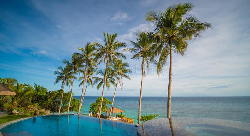 Outdoor swimming pool in a tropical country Philippines with palm trees. Evening time royalty free stock image