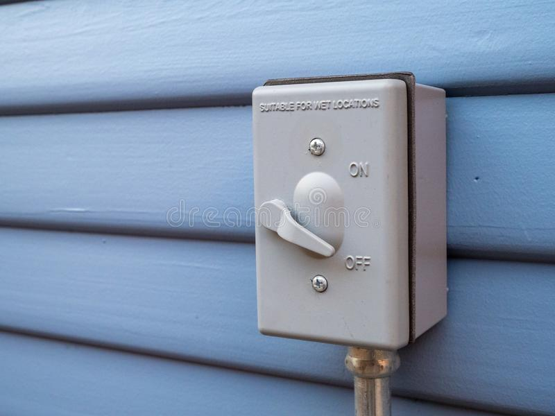 Outdoor switch plug pointed to off position, suitable for wet locations warning. Outdoor switch plug pointed to the off position, suitable for wet locations stock photo