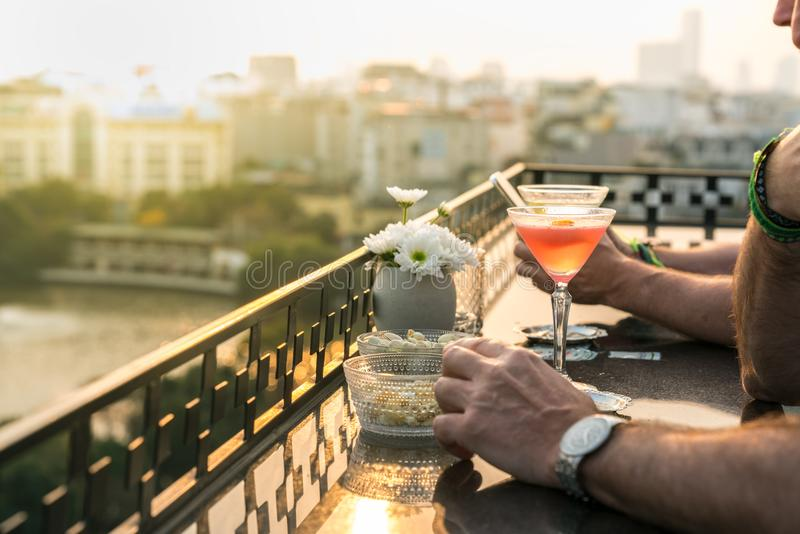 Outdoor table in a cafe and bar with an orange cocktail and man hands closeup. Urban cityscape and lake on background. Brilliant s stock photo