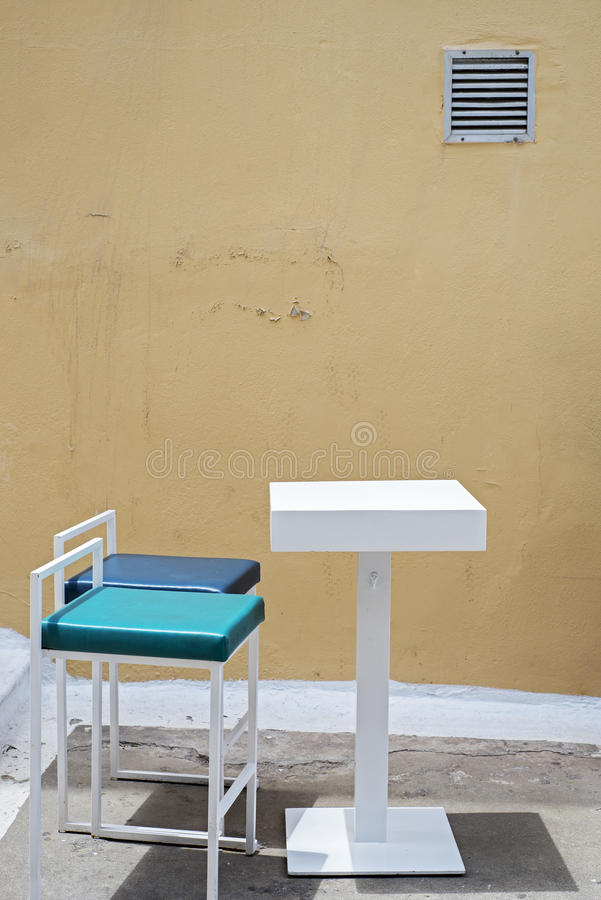 Outdoor table and two chairs near the grunge wall stock photo