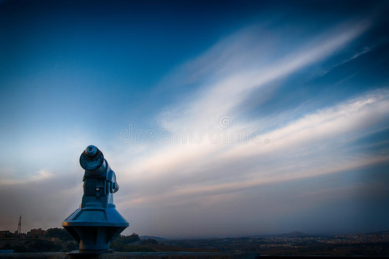 An outdoor telescope with a blue sky and wispy clouds in the background stock photos