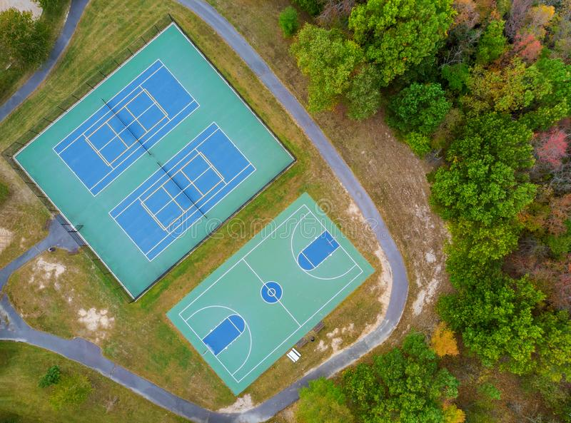Outdoor tennis court and basketball field in the park from a height in autumn. Outdoor tennis green court and basketball field in the park from a height in royalty free stock photography