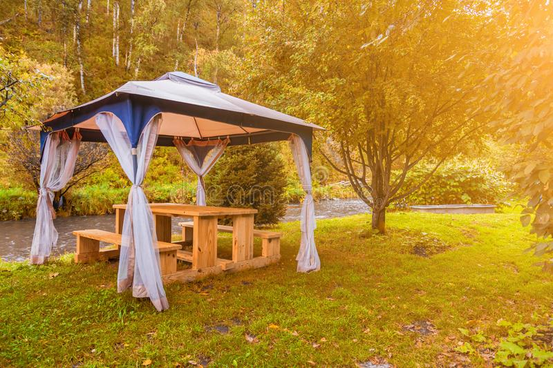 Outdoor tent with furniture in the forest with trees and yellow grass during an event, wedding or a celebration on a warm indian stock photos
