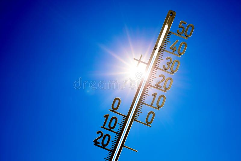 Summer heat. An outdoor thermometer against the blue sky and the summer sun royalty free stock photography