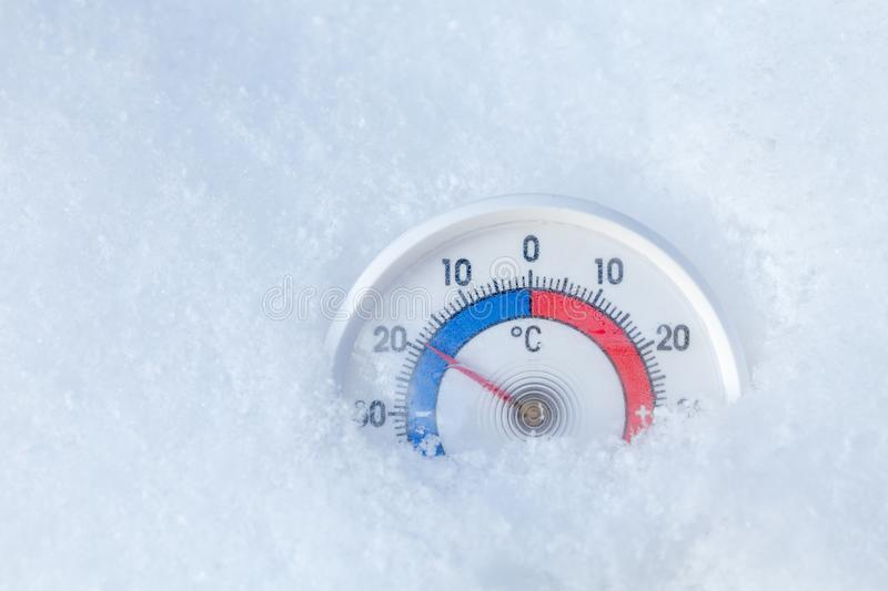 Outdoor thermometer in snow shows minus 19 Celsius degree freezing winter weather concept. Thermometer with celsius scale placed in a fresh snow showing sub-zero royalty free stock image