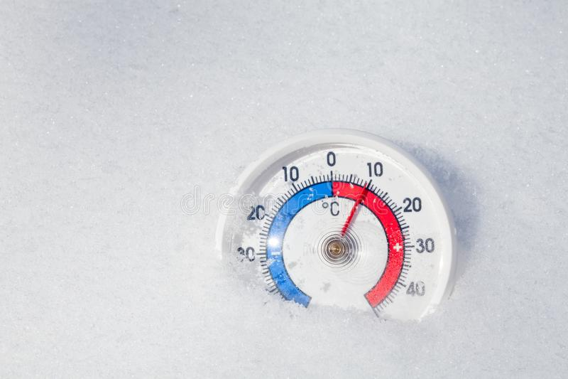 Outdoor thermometer in snow shows warm temperature spring weathe royalty free stock photos