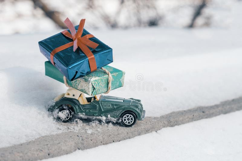 Outdoor toy vintage retro car with gifts for Christmas and New Year, car on a snowy road. Sunny frosty winter day, a lot of snow royalty free stock photos
