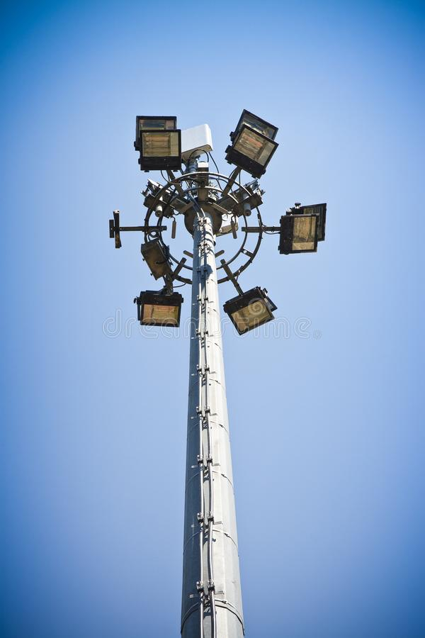 Outdoor train station lights and telecommunication tower against. Blue sky. Circle of bulbs, cell phone gsm antennas on tall metal pole stock photos