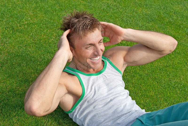 Outdoor training. Young man doing sit-ups. On green grass stock image