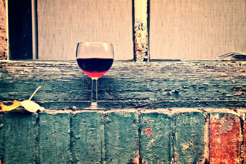 Outdoor urban still life with a glass of red wine. Vintage process royalty free stock photos