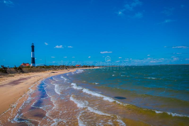 Outdoor view of Atlantic ocean waves on the beach at Montauk Point Light, Lighthouse, located in Long Island, New York. Suffolk County, in a beautiful blue sky stock images
