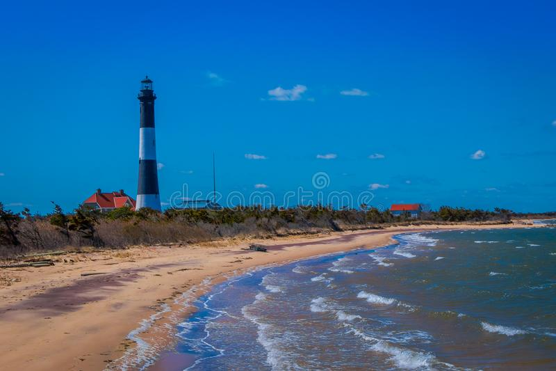 Outdoor view of Atlantic ocean waves on the beach at Montauk Point Light, Lighthouse, located in Long Island, New York. Suffolk County, in a beautiful blue sky stock image