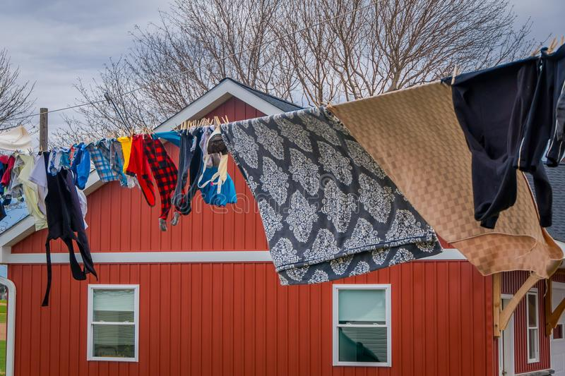 Outdoor view of clothes of Amish drying in the sun and air after laundry with a wooden red house background in Lancaster. Pennylvania stock image