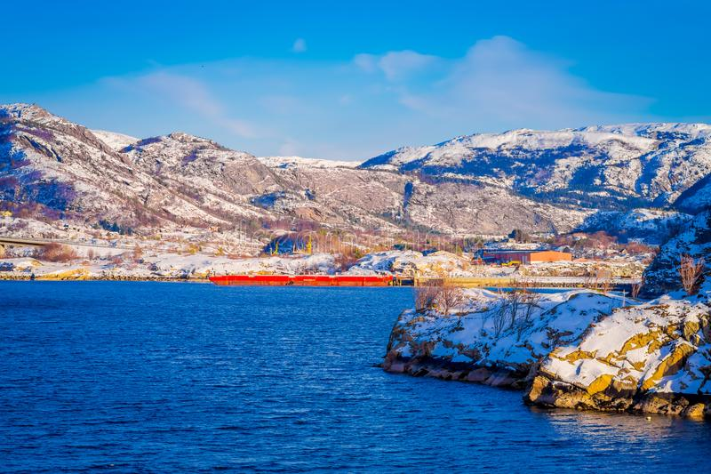 Outdoor view of huge red boat in a shrore with wooden houses a long in the coast from Hurtigruten voyage, Northern. Norway, in a sunny day and blue sky stock photography