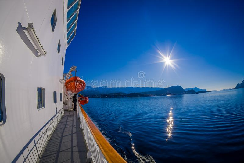 Outdoor view of Hurtigruten cruise, view from deck with a life boat in case an accident. In a gorgeous sunny day with blue sky, in Norway royalty free stock image