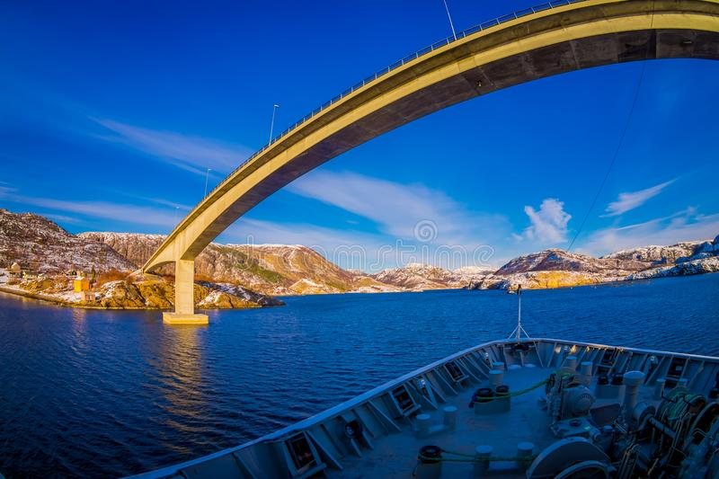 Outdoor view of hurtigruten Ship cruise, frontside with a huge bridge in front. Sailing in a blue sky in Norway stock photo