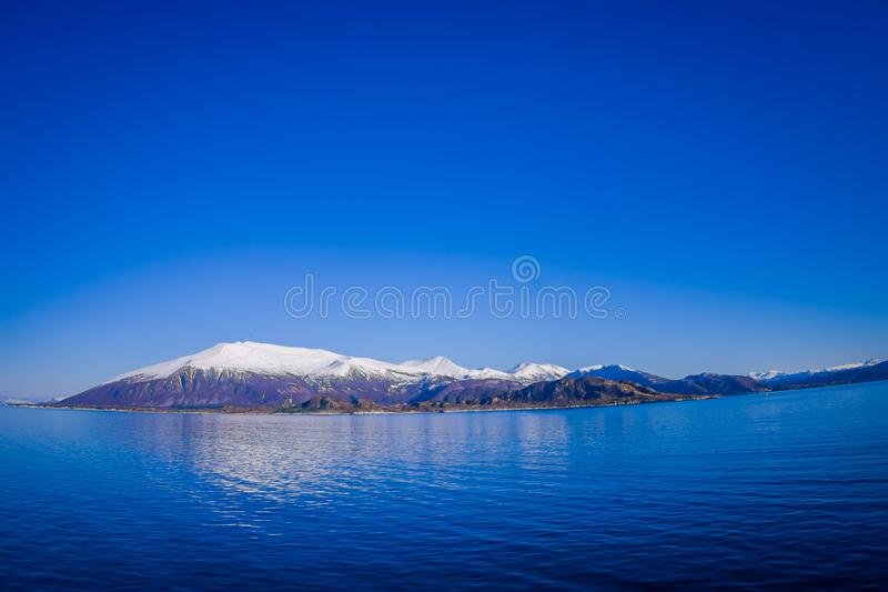 Outdoor view of mountain range in Norway. The beautiful mountain covered partial with snow in Hurtigruten region in. Norway stock photo